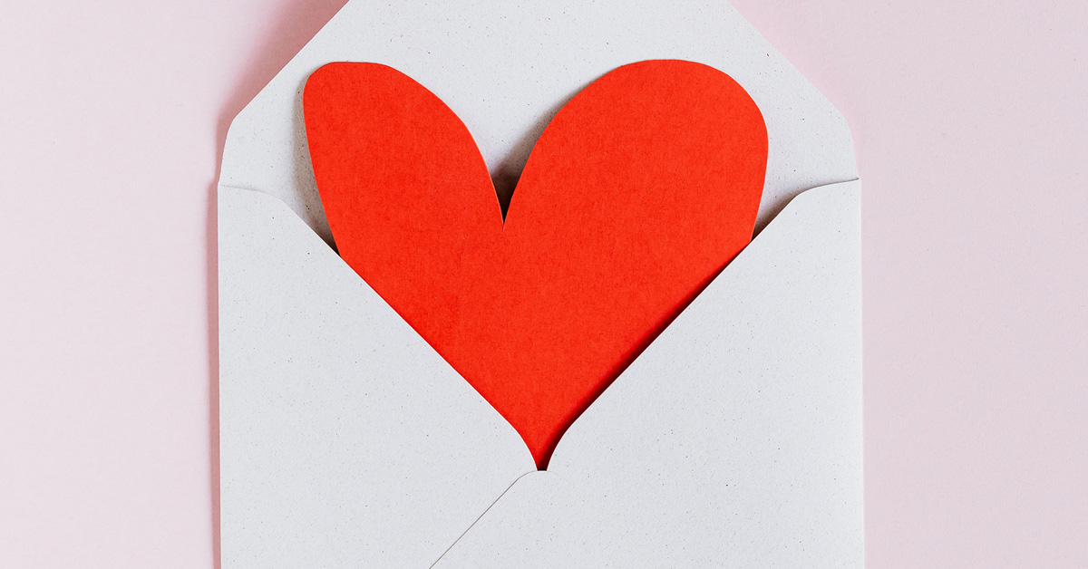 Open envelope with a red paper heart inside